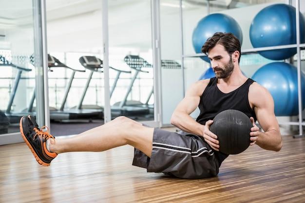 Hombre haciendo ejercicio con balón medicinal en el estudio