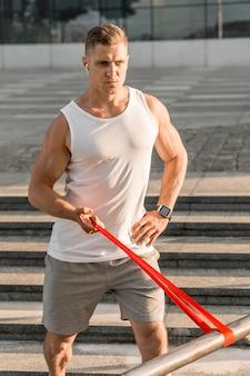 Hombre haciendo ejercicio con una banda roja de estiramiento