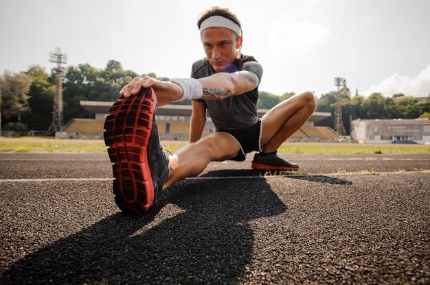Hombre haciendo estiramientos en la pista de atletismo