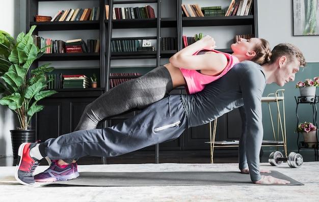 Hombre haciendo flexiones con mujer en la columna vertebral