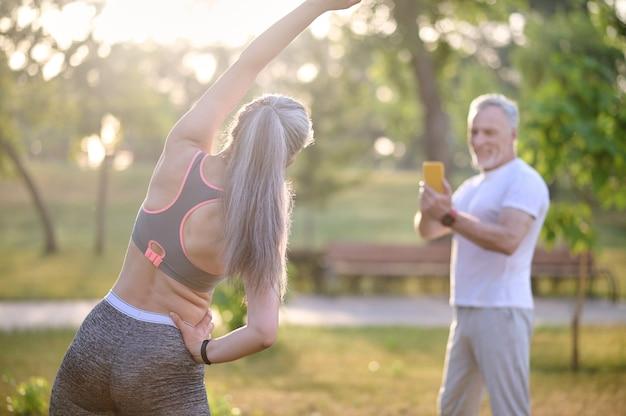 Un hombre haciendo una foto de su esposa mientras ella hace ejercicio.