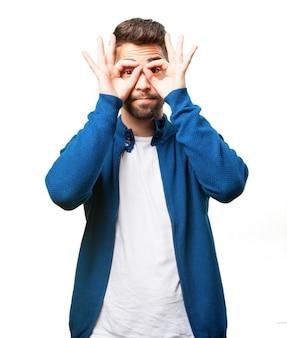 Hombre haciendo gafas con sus dedos