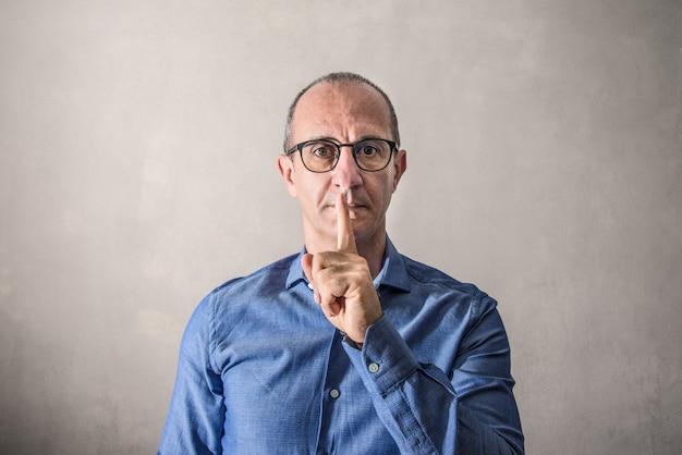 Hombre haciendo el gesto de silenciar