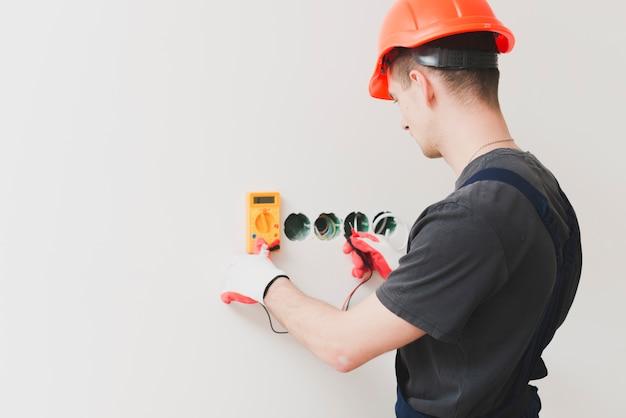 Hombre haciendo medida de voltaje de cable