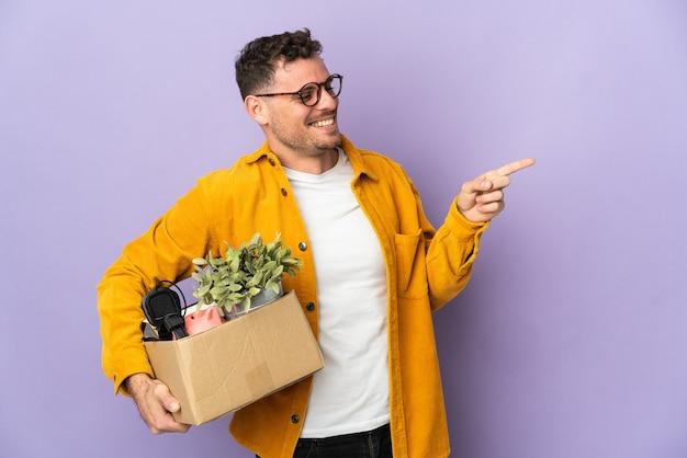 Hombre haciendo un movimiento mientras recoge una caja llena de cosas.