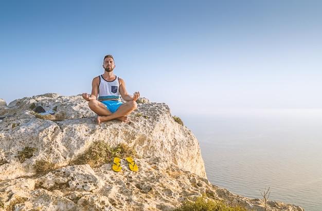 Hombre haciendo postura de loto y meditando