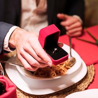 Hombre haciendo propuesta en mesa festiva.