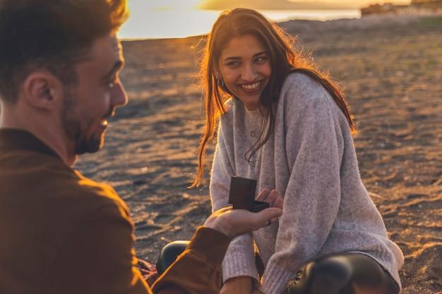 Hombre haciendo propuesta a mujer bonita en la orilla del mar de arena