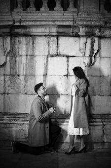 Hombre haciendo propuesta a mujer en calle.