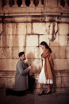 Hombre haciendo propuesta a mujer joven en calle.