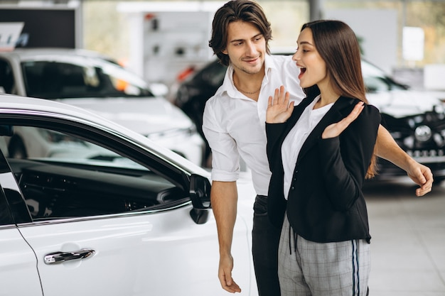 Hombre haciendo un regalo para su mujer en una sala de exposición de automóviles
