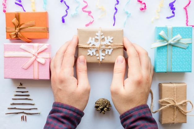 Hombre haciendo regalos de navidad sobre un fondo blanco.