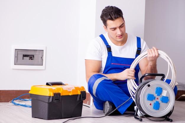 Hombre haciendo reparaciones eléctricas en casa