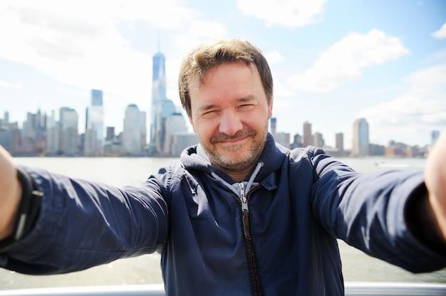 Hombre haciendo selfie con los rascacielos de manhattan en la ciudad de nueva york