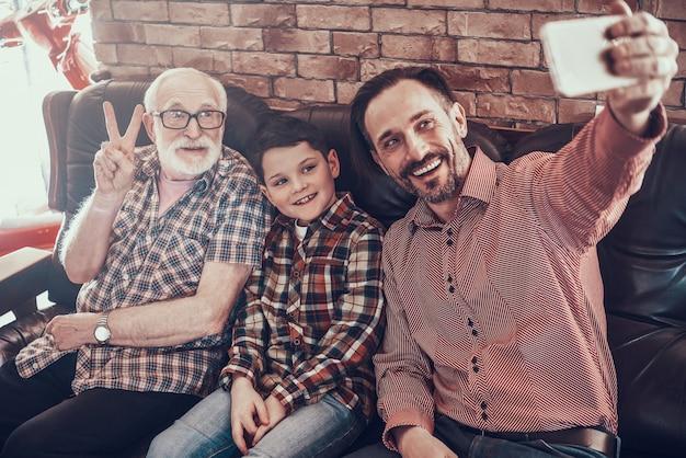 El hombre está haciendo selfie en el sofá con el padre y el hijo