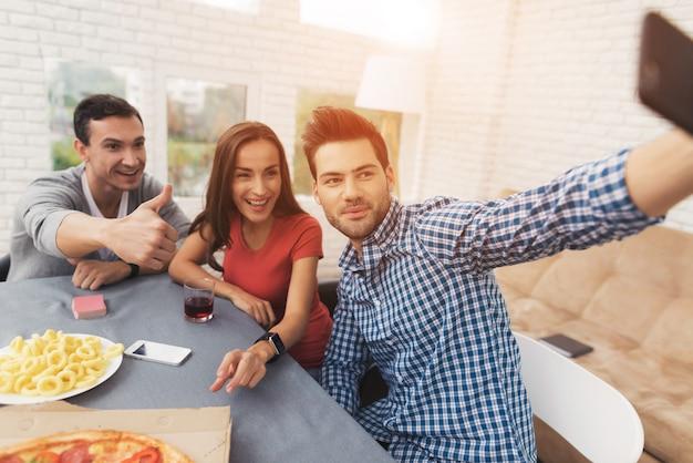 Hombre haciendo selfie con sus amigos en smartphone.