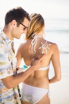 Hombre haciendo un símbolo del sol en la espalda de la mujer mientras aplica una loción de protección solar
