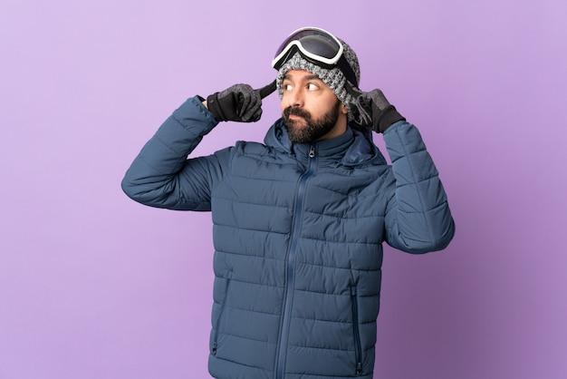Hombre haciendo snowboard sobre pared aislada