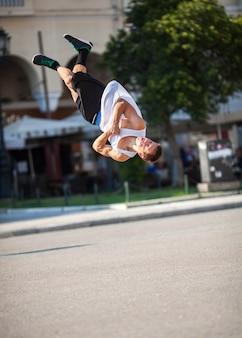 Hombre haciendo trucos acrobáticos en la calle de la ciudad