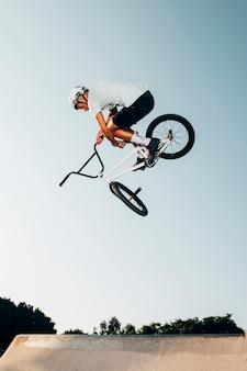 Hombre haciendo trucos al aire libre vista de ángulo bajo