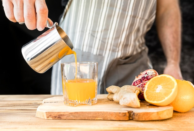 Hombre haciendo una vista frontal de jugo de naranja