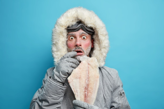 Hombre helado conmocionado emocional vestido con ropa de abrigo de invierno sostiene que el pescado congelado se siente muy frío durante la baja temperatura en el lugar norte.