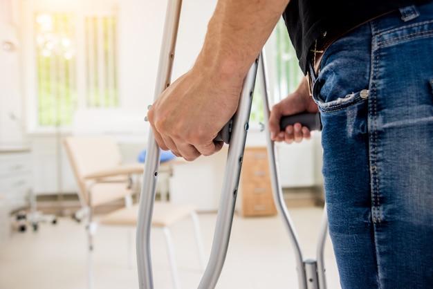 Hombre herido tratando de caminar con muletas en el hospital.