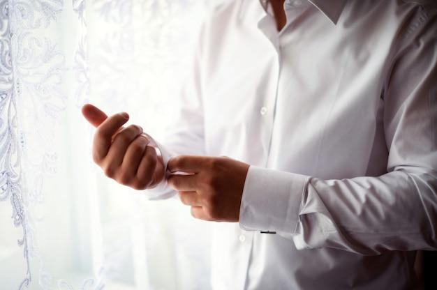 El hombre hermoso abotona su camisa blanca que se coloca en la ventana por la mañana para la ceremonia de boda.