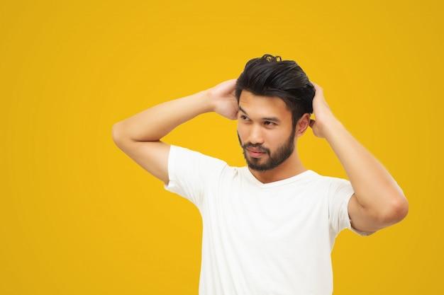 Hombre hermoso asiático con un bigote, sonriendo y riendo aislado sobre fondo amarillo