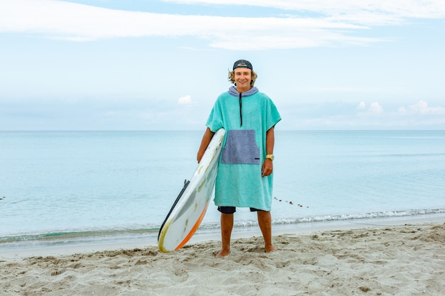 El hombre hermoso camina con la tabla de surf en blanco blanca espera la onda para surfear el lugar en la orilla del mar del océano.