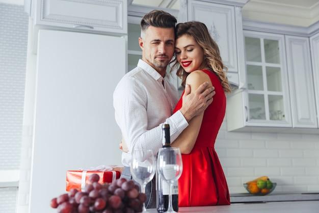 Hombre hermoso confidente guiñando un ojo mientras abraza a su mujer encantadora, concepto de día de san valentín