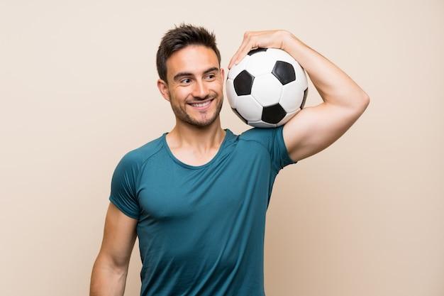Hombre hermoso del deporte sobre el fondo aislado que sostiene un balón de fútbol