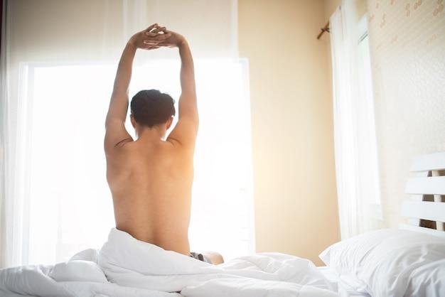El hombre hermoso despierta y levantando la mano en el ben por la mañana