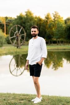 Hombre hermoso en el fondo de un lago en la calle en un día soleado