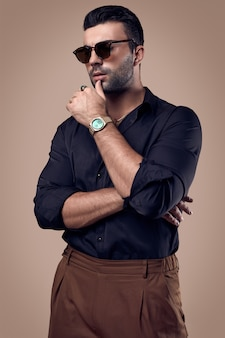 Hombre hermoso hipster bronceado brutal en una camisa negra y gafas