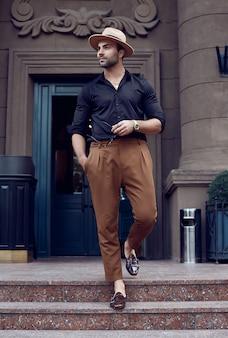 Hombre hermoso inconformista musculoso bronceado brutal hermoso posando en las calles