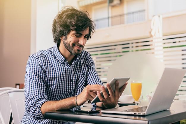 Hombre hermoso joven en el café, sosteniendo una tableta y trabajando en línea con su computadora portátil