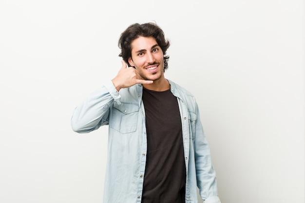 Hombre hermoso joven contra una pared blanca que muestra un gesto de llamada de teléfono móvil con los dedos.