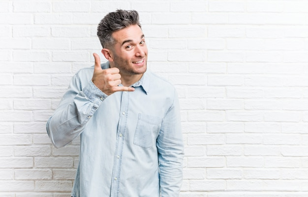 Hombre hermoso joven contra una pared de ladrillos que muestra un gesto de llamada de teléfono móvil con los dedos.