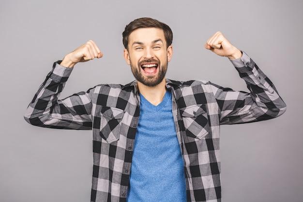Hombre hermoso joven feliz que gesticula y que mantiene la boca abierta mientras que se opone a la pared blanca gris.