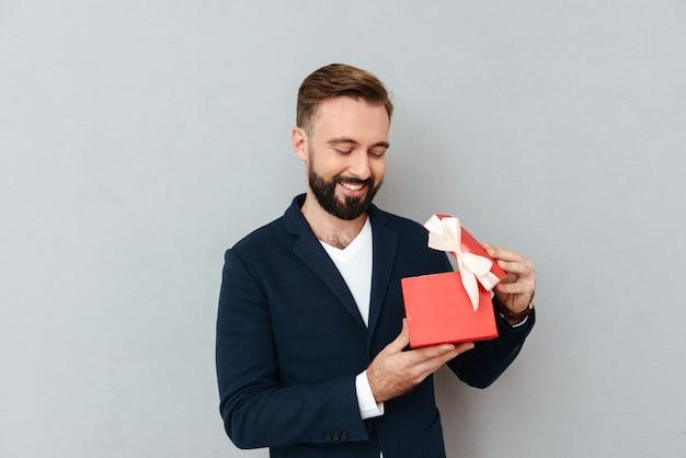 Hombre hermoso joven feliz que mira el regalo rojo aislado