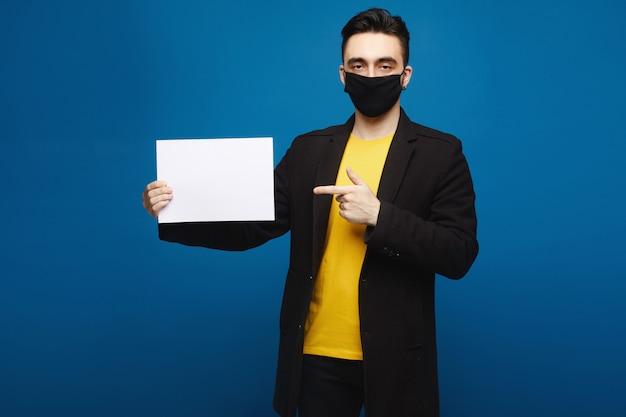 Hombre hermoso joven en la máscara protectora negra que sostiene la hoja de papel en blanco y que señala en ella, aislada en el fondo azul. concepto de promoción. concepto de salud