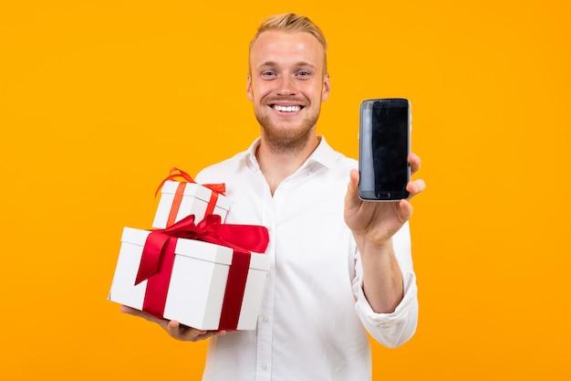 El hombre hermoso joven con el pelo rubio en la camisa blanca sostiene la caja blanca con el regalo y llama el teléfono aislado en amarillo