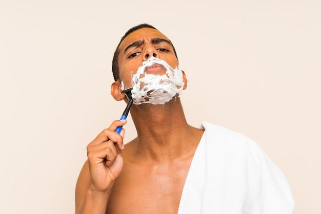 Hombre hermoso joven que se afeita la barba sobre la pared aislada
