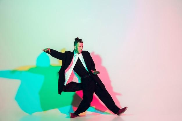Hombre hermoso joven que baila hip-hop, estilo callejero aislado en estudio