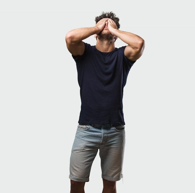 Hombre hermoso joven que se coloca frustrado y desesperado, enojado y triste con las manos en la cabeza