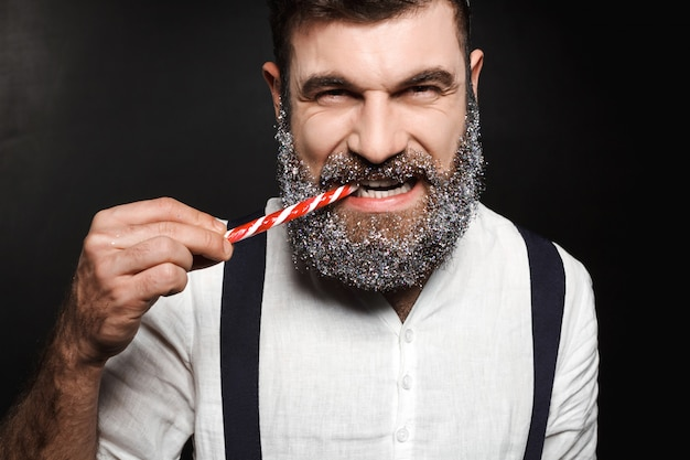 Hombre hermoso joven que come el caramelo de la navidad sobre negro.