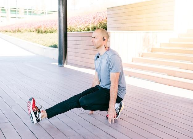 Hombre hermoso joven que estira ejercicio en el parque