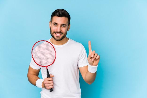 Hombre hermoso joven que juega a bádminton aislado que muestra el número uno con el dedo