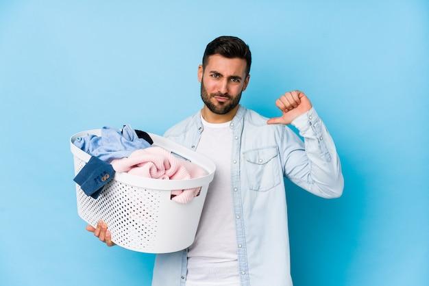 El hombre hermoso joven que lava la ropa aislada se siente orgulloso y seguro de sí mismo, ejemplo a seguir.
